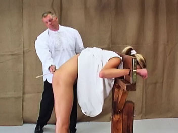 Caned in a guillotine. Dzejisis has been extra naughty and is placed in a guillotine to receive her caning. The headmaster lifts her dress and uses his cane to turn her bare booty a pretty shade of pink.  The caning is completed only when the headmaster decides her booty is t