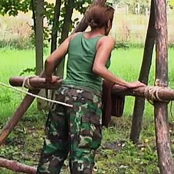 Eva knew being in the army would be painful but she never expected this.  When she fails to properly shoot a target, her taskmaster calls her over places her against a makeshift tree and uses his cane to teach her a lesson.  Eva cries out with each caning