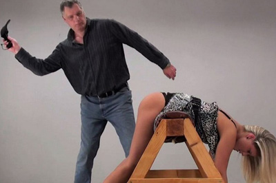 He bends her over, a rubber paddle waiting for bare smooth ass. He brings it down hard on her round bottom, instantly turning her milky skin neon red.